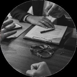 händer, papper och handfängsel på ett bord